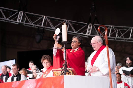 Rev. Phoebe Roaf raises the waifer and cup during communion at her consecration ceremony.