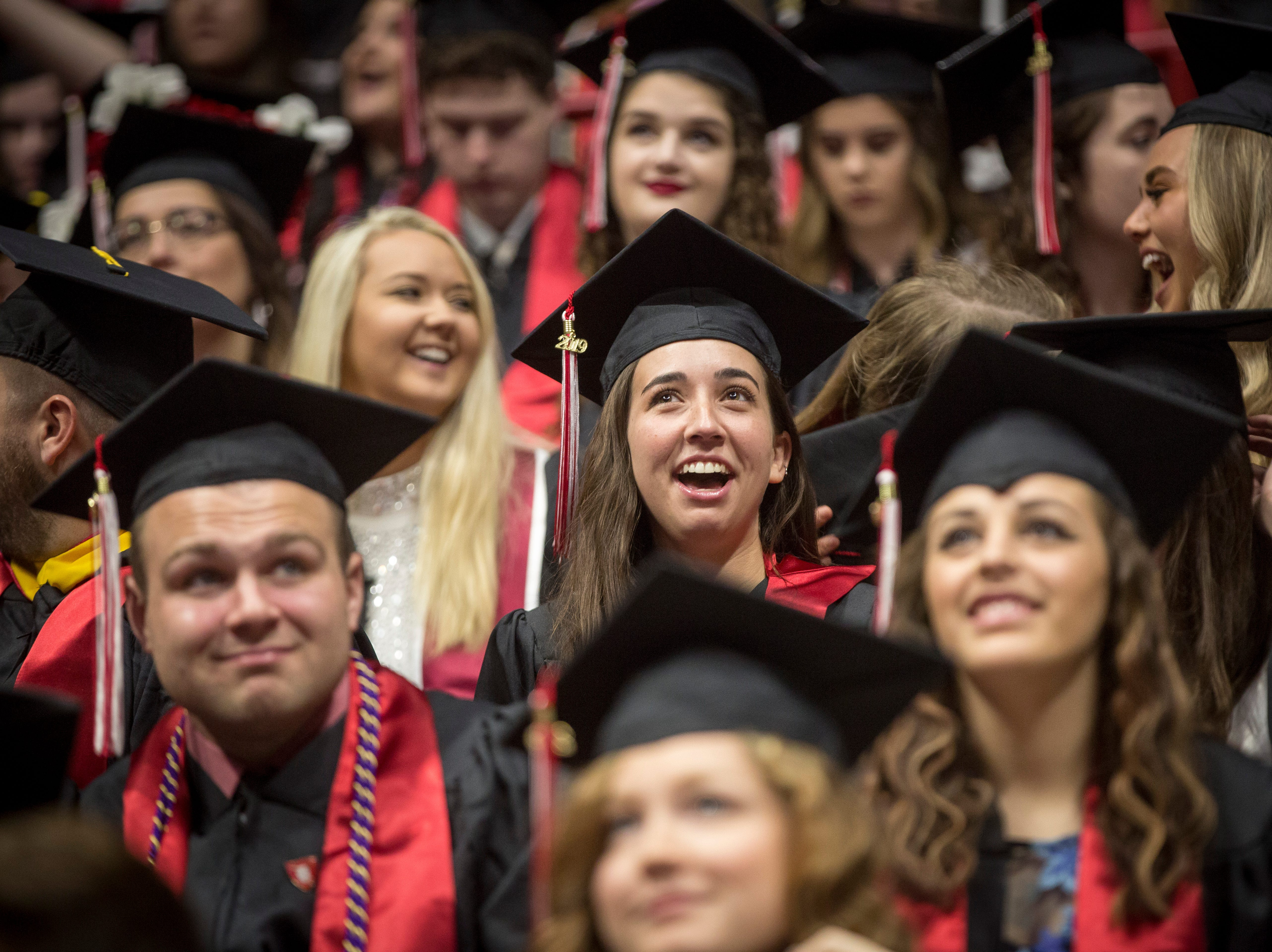 Graduates react to the big screen in the center of the arena which highlighted cheering students and more during the ceremony on May 4 during Ball State University's Spring Commencement inside Worthen Arena. Inclement weather moved the ceremony indoors.