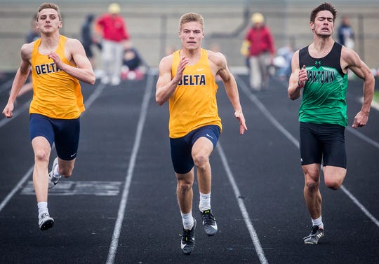 Delta's Grady Foreman, left, and Delta's Wesley Stitt, center compete in the 100m dash during the Delaware County Track Meet at Delta High School Friday, May 3, 2019.