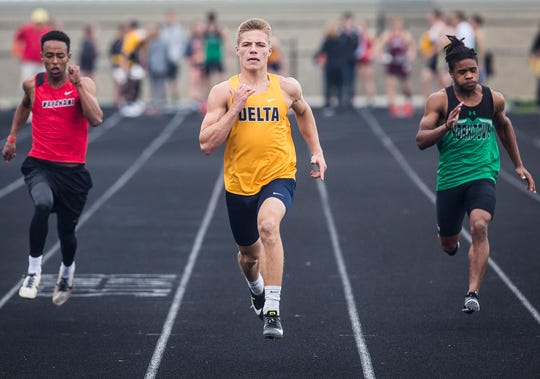 Delta's Wesley Stitt, center, sprints during the Delaware County Track Meet at Delta High School Friday, May 3, 2019.
