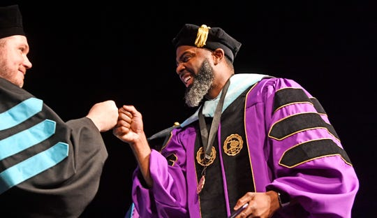 Dr. Ryan Longnecker, online Ed.D. program director, left, fist bumps with former Tennessee Titan Kevin Dyson, who graduated with his Doctor of Education (Ed.D.) in leadership and professional practice Saturday, May 4, 2019, in Nashville, Tenn.