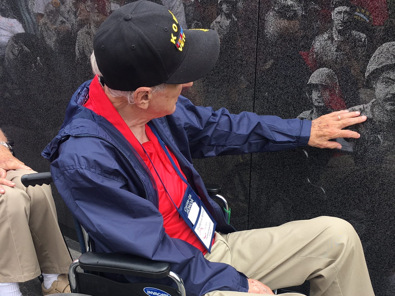 Korean War veteran Frederick Penrod touches images on the granite wall Saturday, May 4, 2019, while on a trip with the Collier-Lee Honor Flight.
