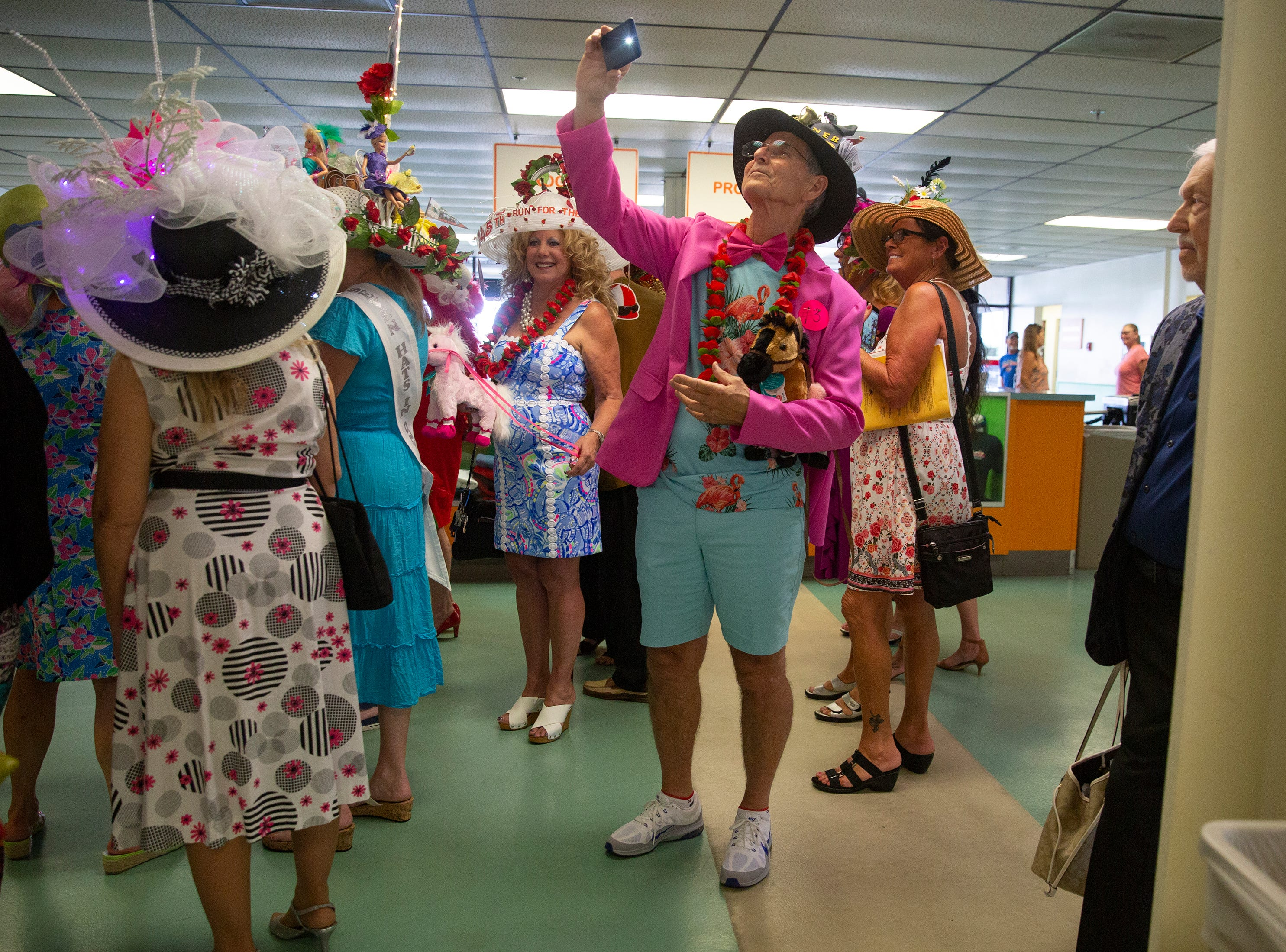 David East of Estero, takes photos of fellow contestants during the annual Best Derby Hat competition with a tiny hat, Saturday, May 4, 2019, at Naples Fort Myers Greyhound Racing and Poker in Bonita Springs.