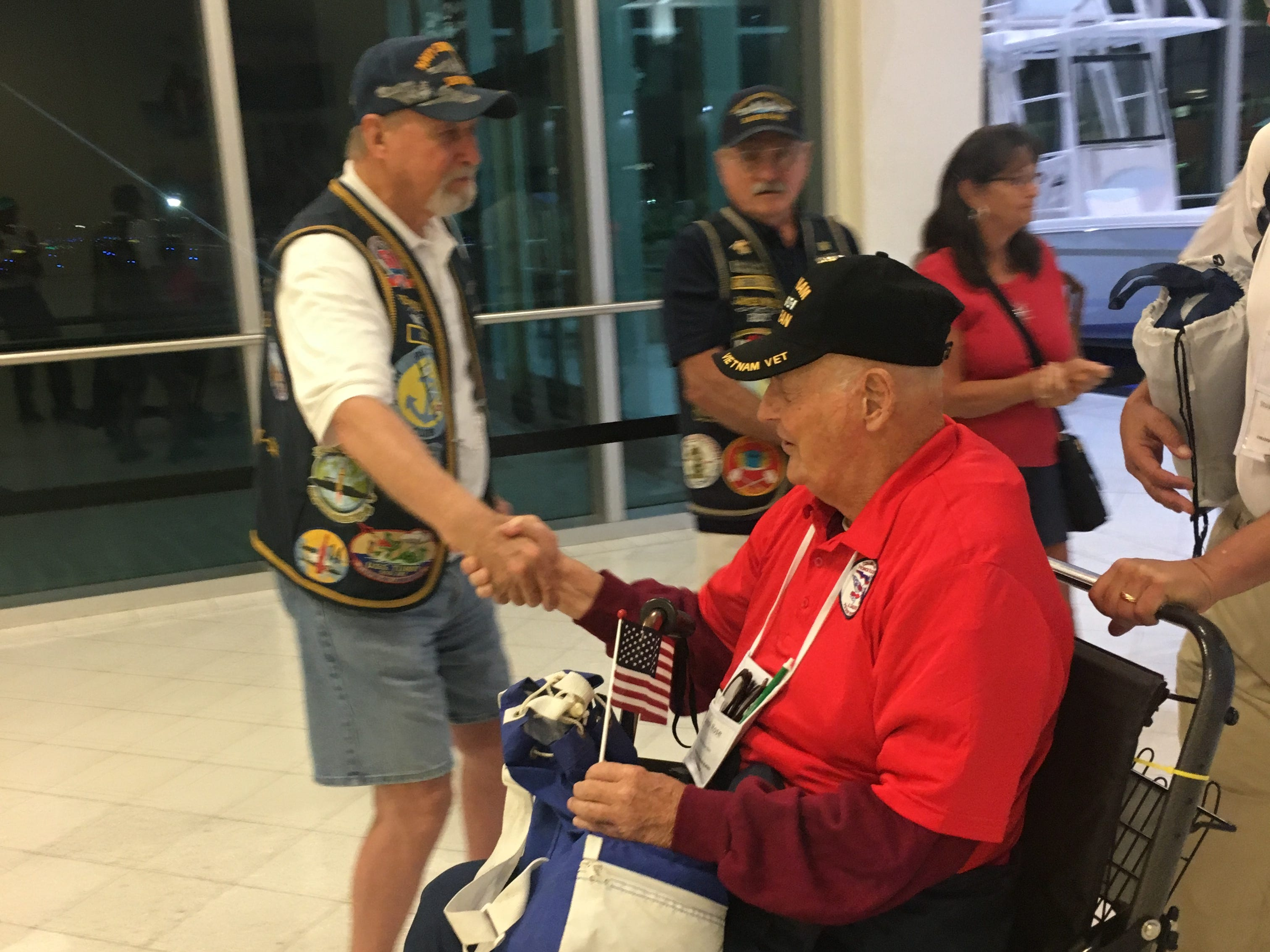 Bob Duncan, standing, a U.S. Navy veteran from Cape Coral, greets Vietnam veteran Joseph Rose as Rose prepares to board a Collier-Lee Honor Flight to Washington, D.C. Saturday, May 4, 2019, at Southwest Florida International Airport.