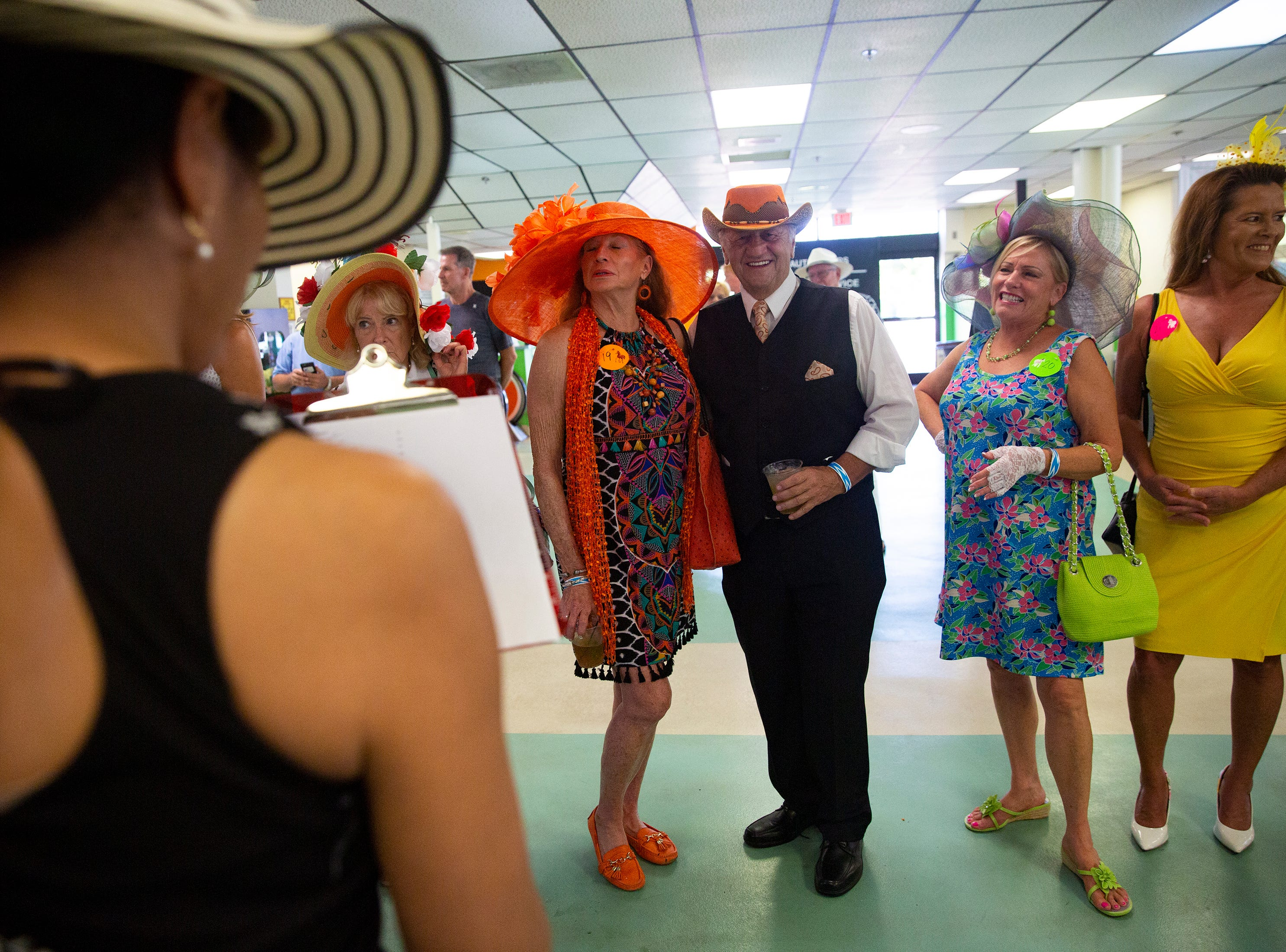 Judges look over Paulette Klein and Joseph Agril's hat during the judging portion of the Best Derby Hat competition, Saturday, May 4, 2019, at Naples Fort Myers Greyhound Racing and Poker in Bonita Springs.