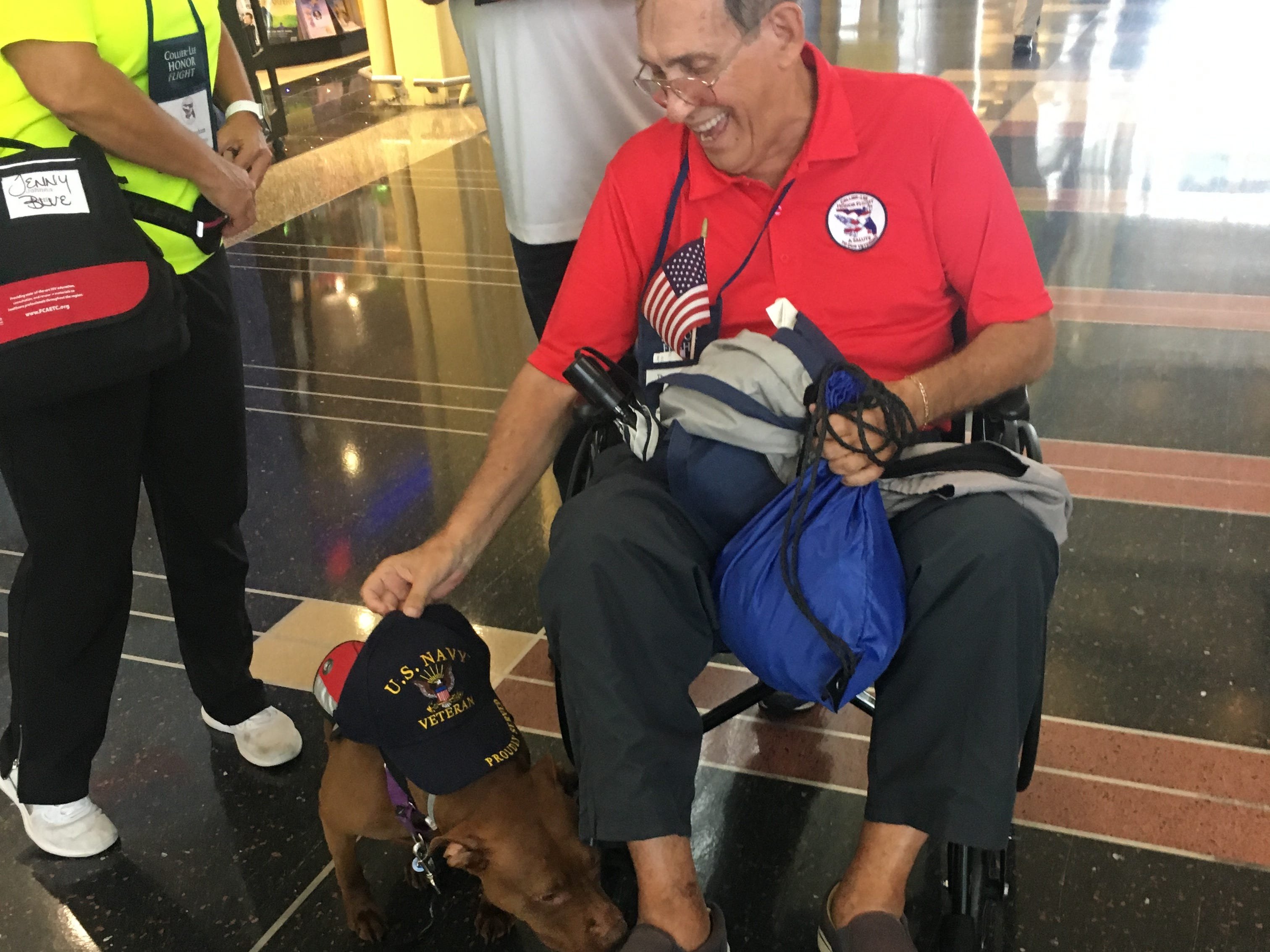 Navy veteran Thomas Henry pets a dog that was part of a welcoming contingent for Collier-Lee Honor Flight at Reagan International Airport on Saturday, May 4, 2019.