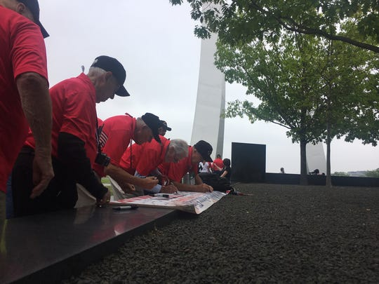 Collier-Lee Honor Flight veterans sign a banner commemorating their trip Saturday, May 4, 2019, to Washington, D.C. The US Air Force Memorial is in the background.