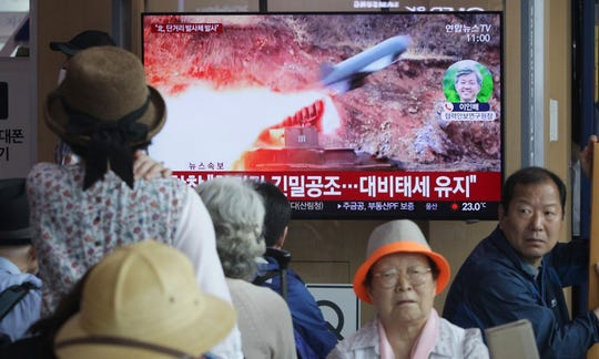 """People watch a TV showing a file footage of North Korea's missile launch during a news program at the Seoul Railway Station in Seoul, South Korea, Saturday, May 4, 2019.  North Korea on Saturday fired several unidentified short-range projectiles into the sea off its eastern coast, the South Korean Joint Chiefs of Staff said, a likely sign of Pyongyang's growing frustration at stalled diplomatic talks with Washington meant to provide coveted sanctions relief in return for nuclear disarmament. The signs read: """"Maintain Readiness."""""""