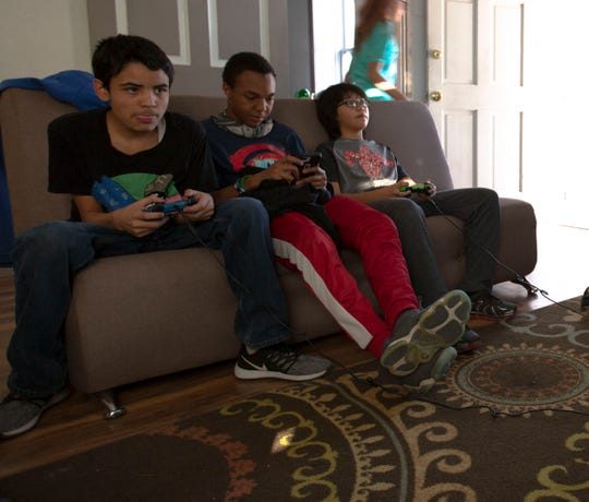 Joseph Contreras, 13, Jai Patterson, 14 , and Denzel Wright, 12, play video games during teen night at the Boys and Girls Club, Friday, May 3, 2019.