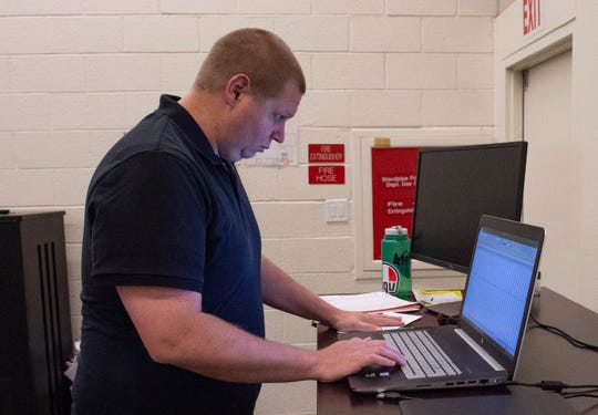 Christopher Aiken, assistant professor in the department of kinesiology and dance, looks over data being collected in a golf study being performed in one of the departments labs at the Activities Center, Thursday May 2, 2019.
