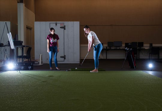 Lauren Brooks, a sophmore and Kineseology major, prepares to take a swing at a golf ball on a putting green with a sensor in it, while Rhiannon Jaramillo stands by with a few more balls for Brooks to hit in a Kinesiology Lab at the Activity Center on Thursday May 2, 2019.