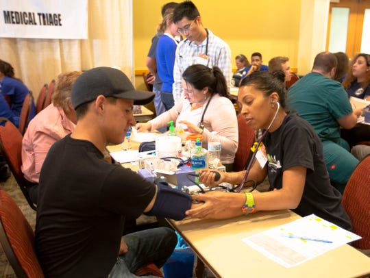 """Paramedic and medical student Carla Tayes, right, takes Cayden Wilson's blood pressure Saturday, May 4, 2019, at the Las Cruces Convention Center, during the New Mexico Mission of Mercy's free dental clinic. Tayes said she heard about the event through school, and knew she wanted to volunteer. Wilson said he hasn't been to a dentist recently because of school, work and traveling. """"It's been an interesting experience jumping around so far,"""" he said."""