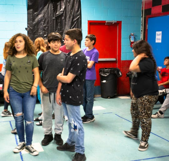 Mia Aguilera, 13, gathers with friends Brian P., 13, and Vicente Burke, 13, Thomas Terrell, Mia Garcia, and Ramon Bustamante, at the Boys and Girls Club during teen night. It was Brian's first time attending teen night. He said his favorite activity so far, was playing basketball.