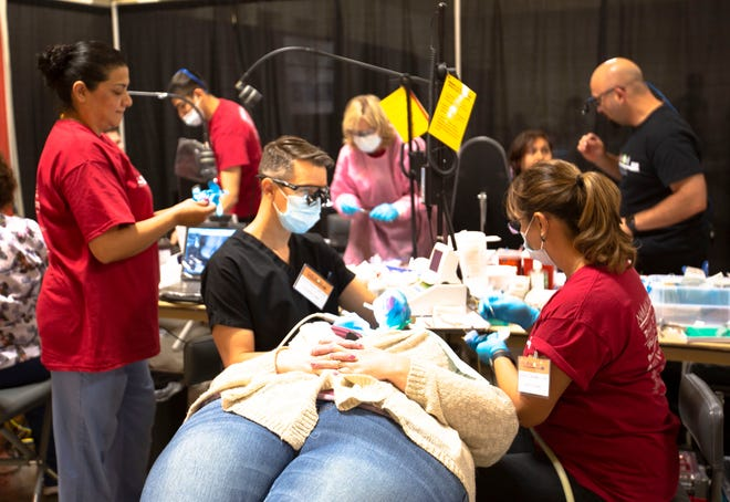 A dentist, along with an assistant, offer care to a patient Saturday May 4, 2019, at the Las Cruces Convention Center, which was transformed into a dental clinic Friday and Saturday. About 500 volunteers came together to offer services this weekend for the Mission of Mercy event.