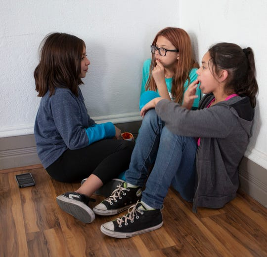 Heaven Wright, center, 13, enjoys snacks with friends Carolina Pacheco, left, and Ariza Contreras, at the Boys and Girls Club Friday May 3, 2019, during teen night. So far, her favorite activity has been laser tag. Pictured from left, Carmina P., 12, Heaven W. 13, and Ariza C., 12.