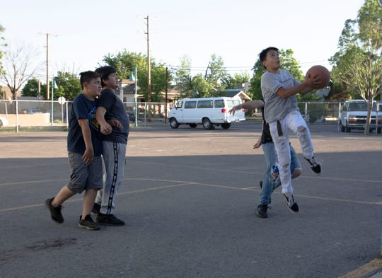 Aiden Burford and Vicente Burke, watch as Isacc Candelaria shoots hoops at the Boys and Girls Club, Friday, May 3, 2019.