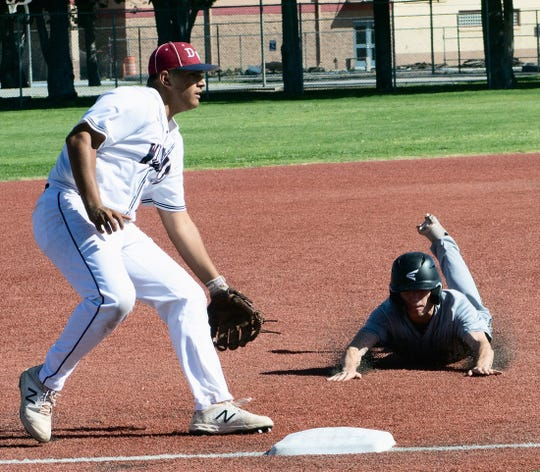 Alamogordo Tiger Collin Kirk begins a slide towards third base, while Deming Wildcat Jacob Morales waits for a throw with which to tag Kirk. Kirk would make it safely to third.