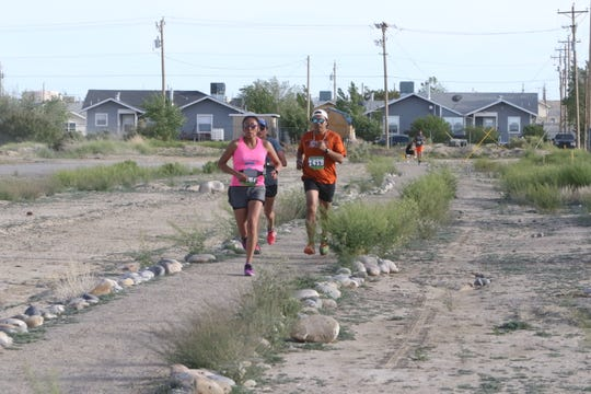 Shiprock Marathon runners in the 5K and 10K races move toward Diné College's south campus Friday in Shiprock.