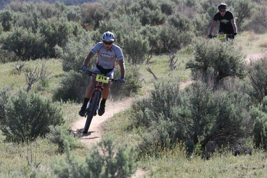 Bicyclists race through sage brush toward the end of the first lap, Saturday, May 4, 2019, during the Alien Run Mountain Bike Race.