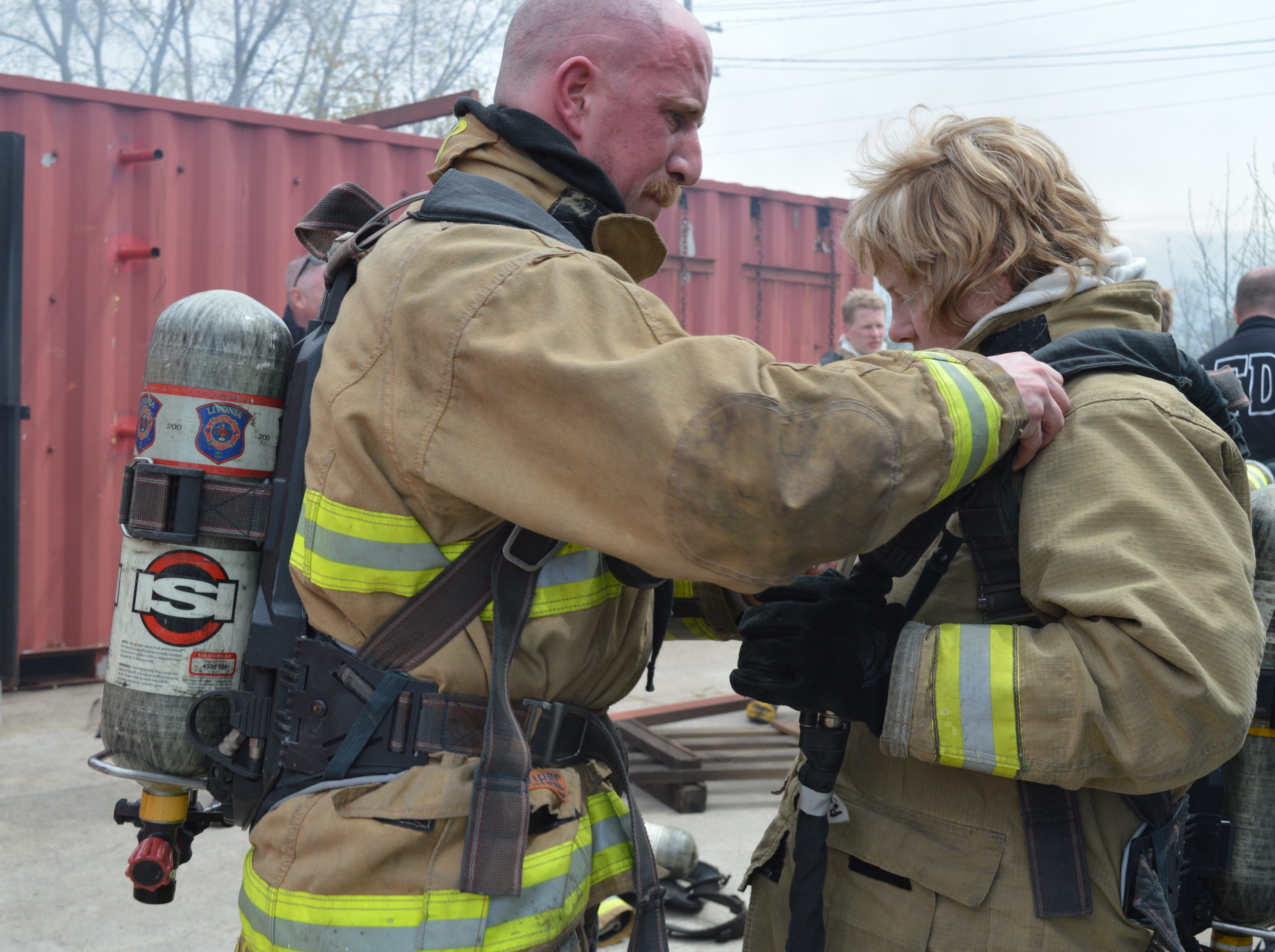 Livonia firefighter Scott Heraty helps Councilwoman Kathleen McIntyre remove some gear after a live burn drill.