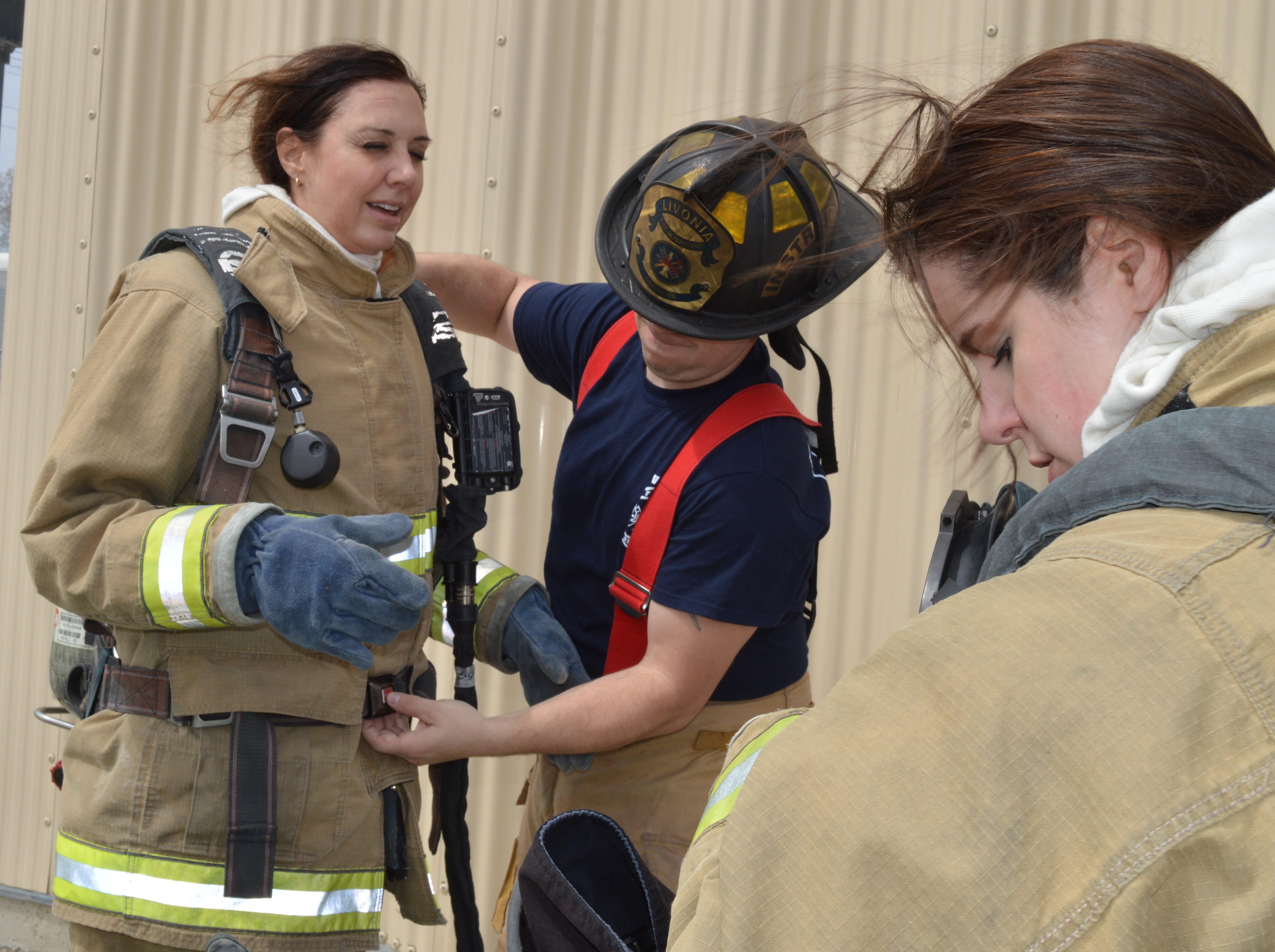 A Livonia firefighter helps state Sen. Dayna Polehanki remove gear after a Fire Ops 101 drill on Saturday, May 4, 2019.  State Rep. Laurie Pohutsky is in the foreground.