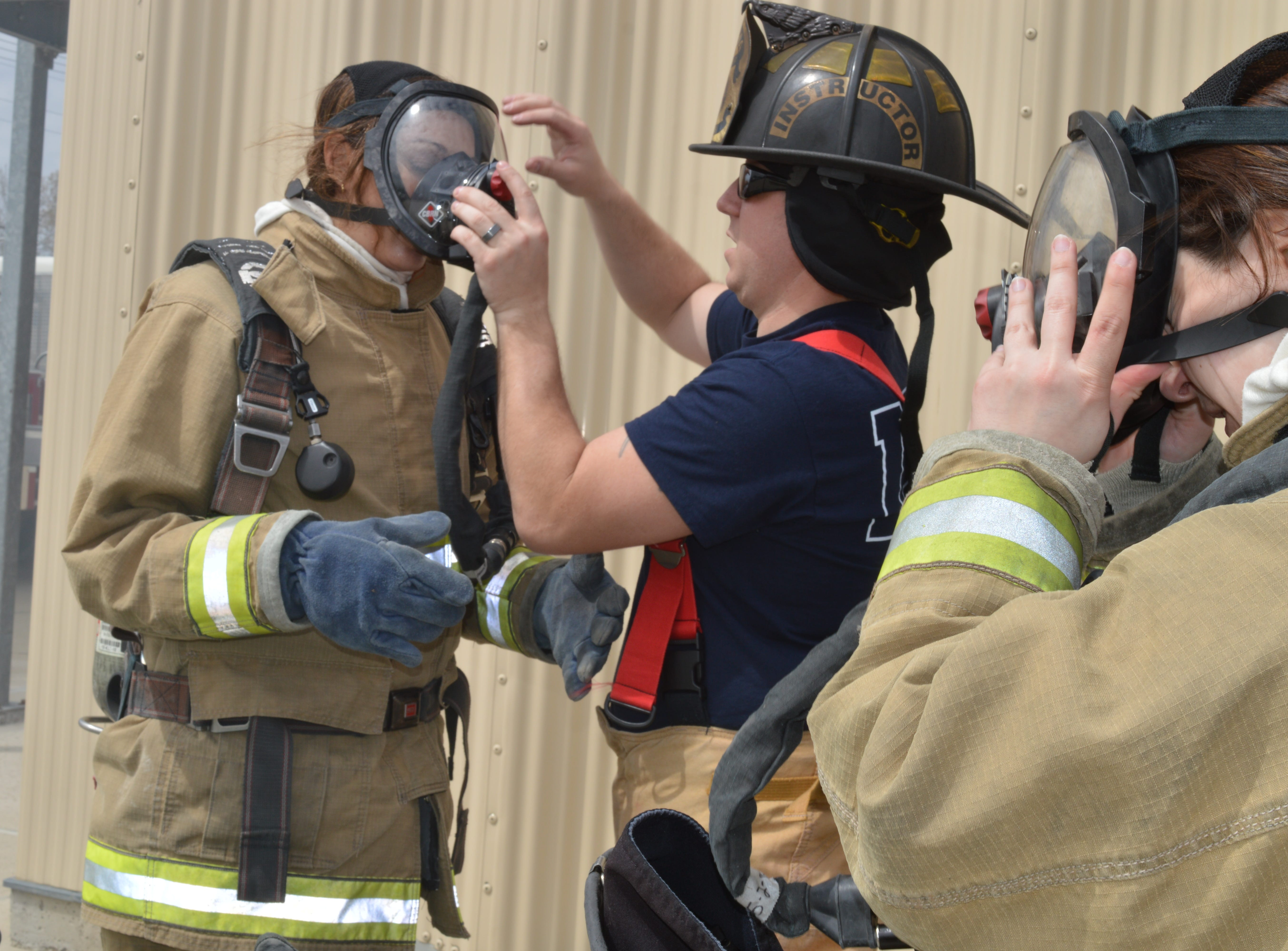 A Livonia firefighter helps state Sen. Dayna Polehanki remove gear after a Fire Ops 101 drill on Saturday, May 4, 2019.