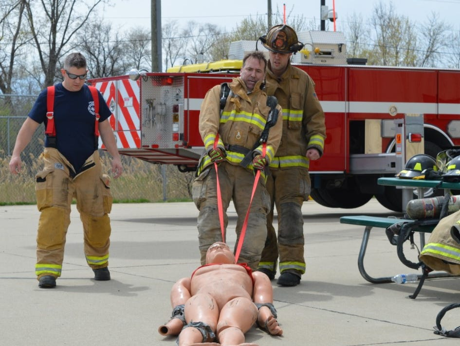 Livonia Councilman Brandon Kritzman drags a dummy during a Fire Ops 101 drill on Saturday, May  4, 2019.