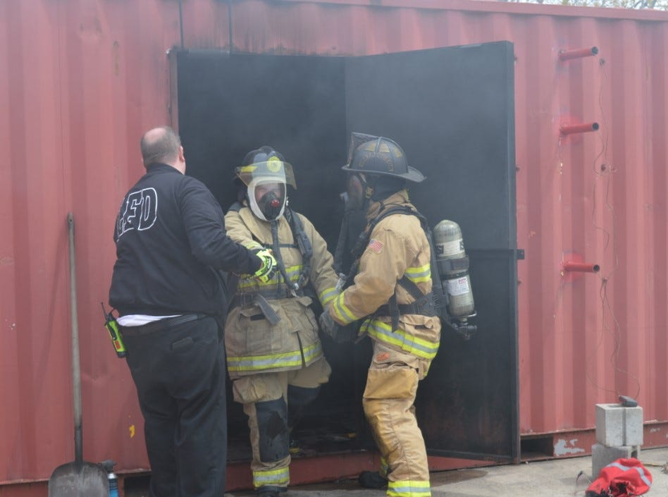 Livonia firefighters guide a Fire Ops 101 participant out of a chamber filled with fire Saturday, May 4, 2019.