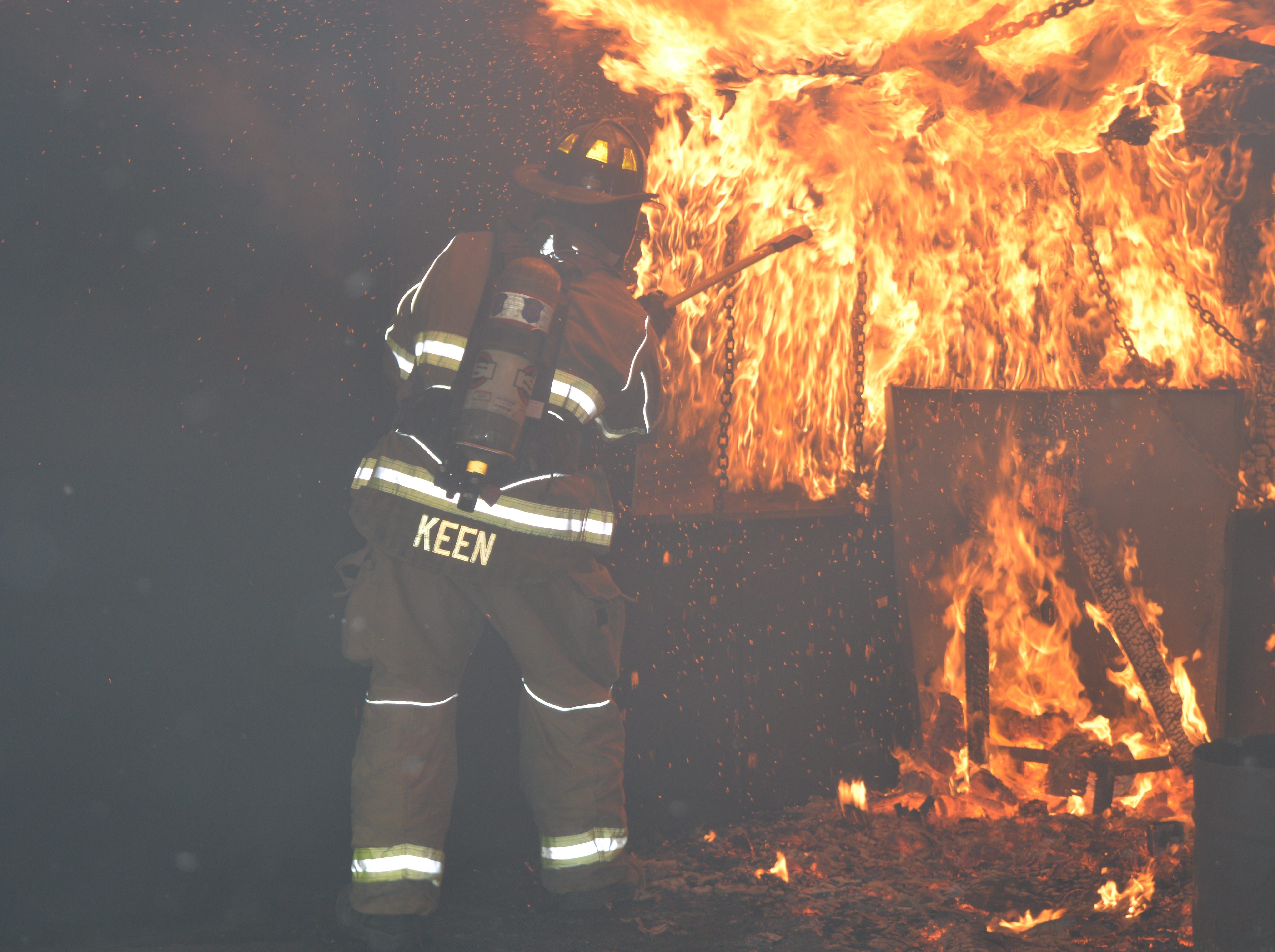 A Livonia firefighter tames a live burn inside a chamber on Saturday, May 4, 2019.