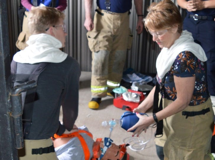 From left to right, Livonia Councilman Scott Bahr and Denise Maier, the city's human resources director, participate in a Fire Ops 101 drill on Saturday, May 5, 2019.