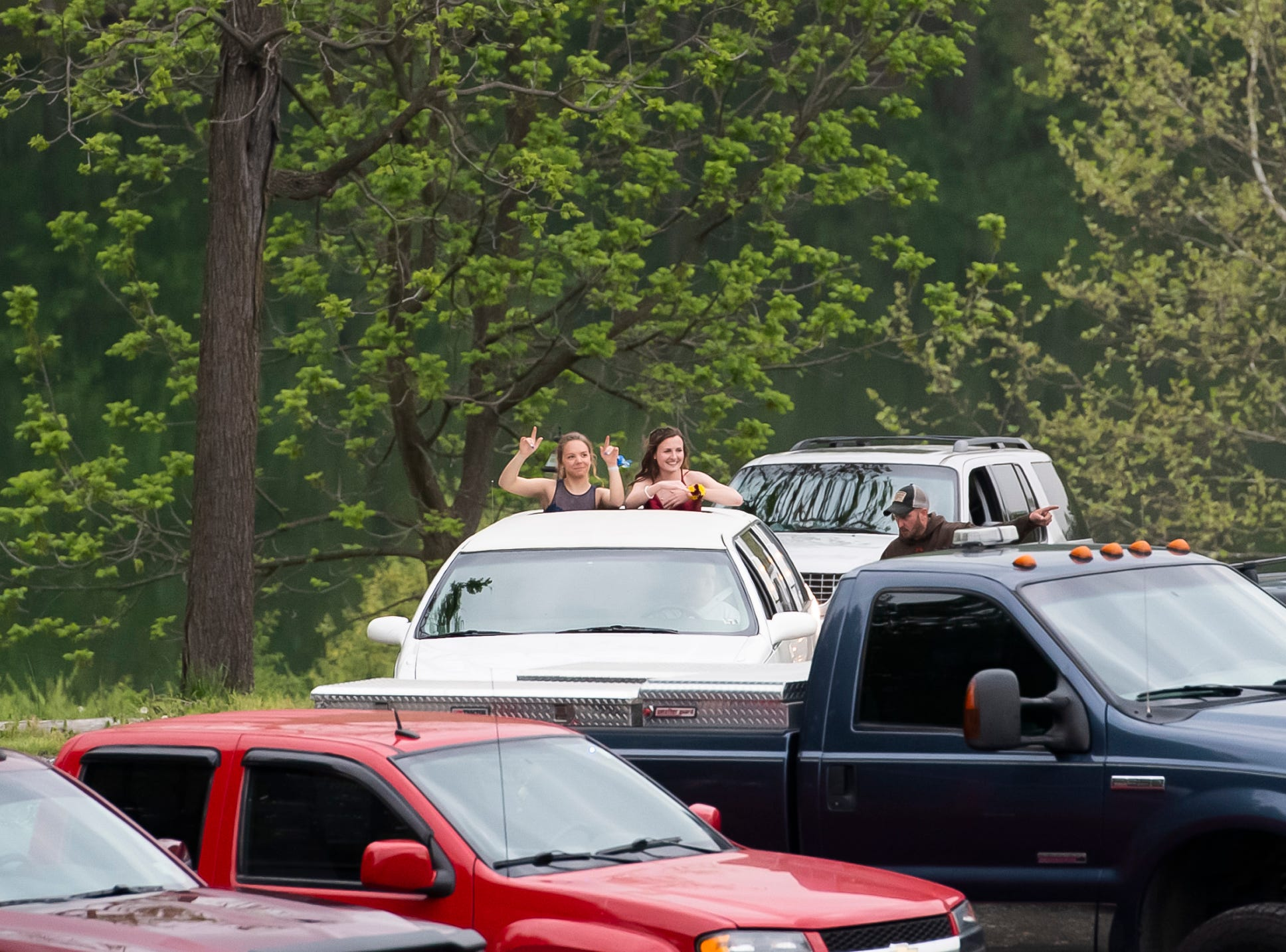 Emily Glass, left, and Sam Schulteis dance along to music through the sunroof of a limo as they arrive at Biglerville High School's prom at the Lodges at Gettysburg on Friday, May 3, 2019.