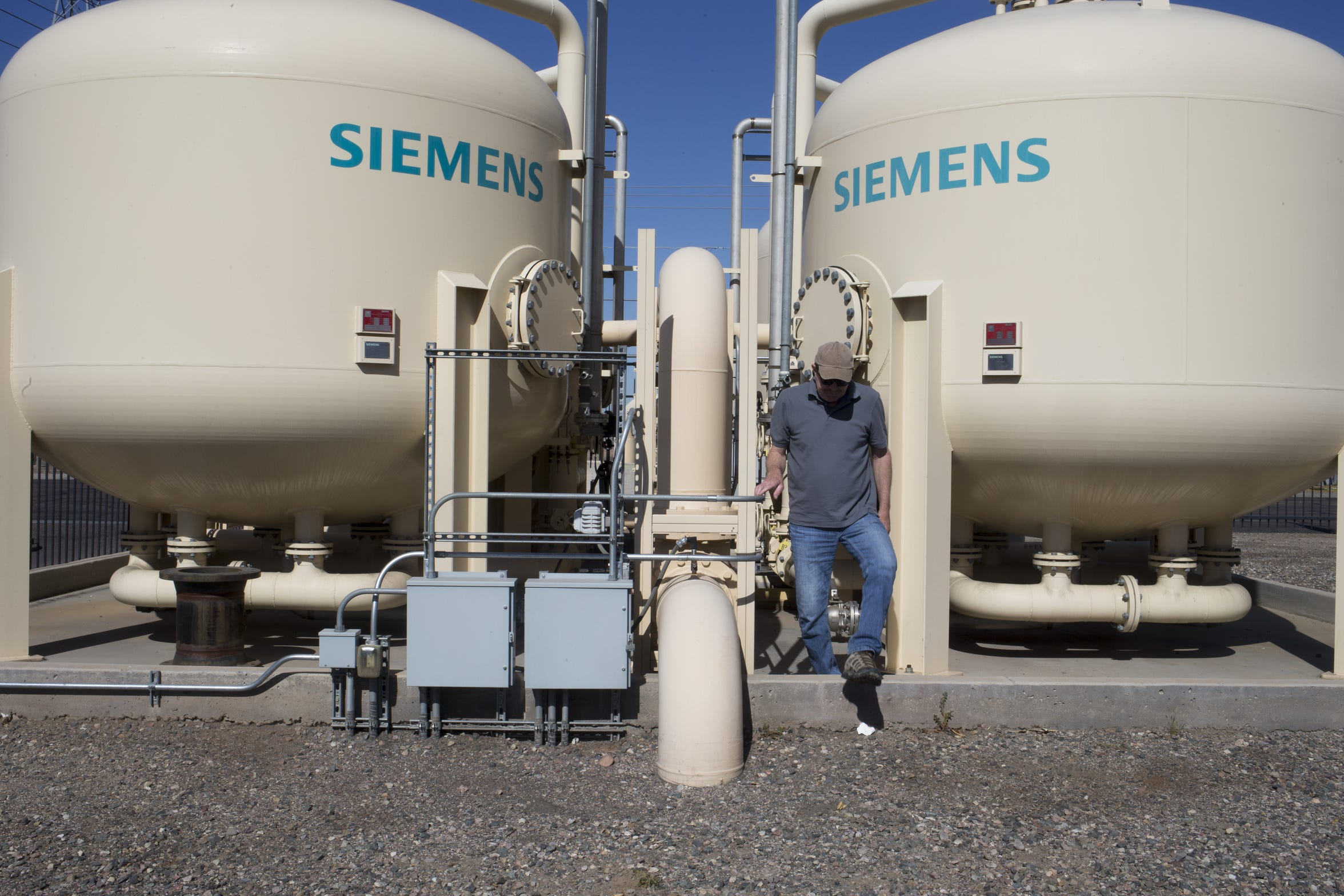 Joel Peterson of the firm Synergy Environmental works at the treatment system at one of the Roosevelt Irrigation District's wells, at 35th Avenue and Sherman Street in Phoenix.