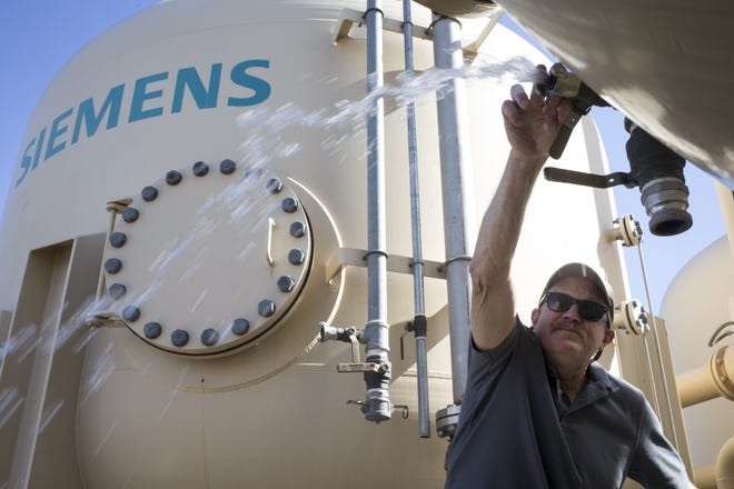 Joel Peterson of the firm Synergy Environmental bleeds air from the treatment system on a well at 35th Avenue and Sherman Street in Phoenix.