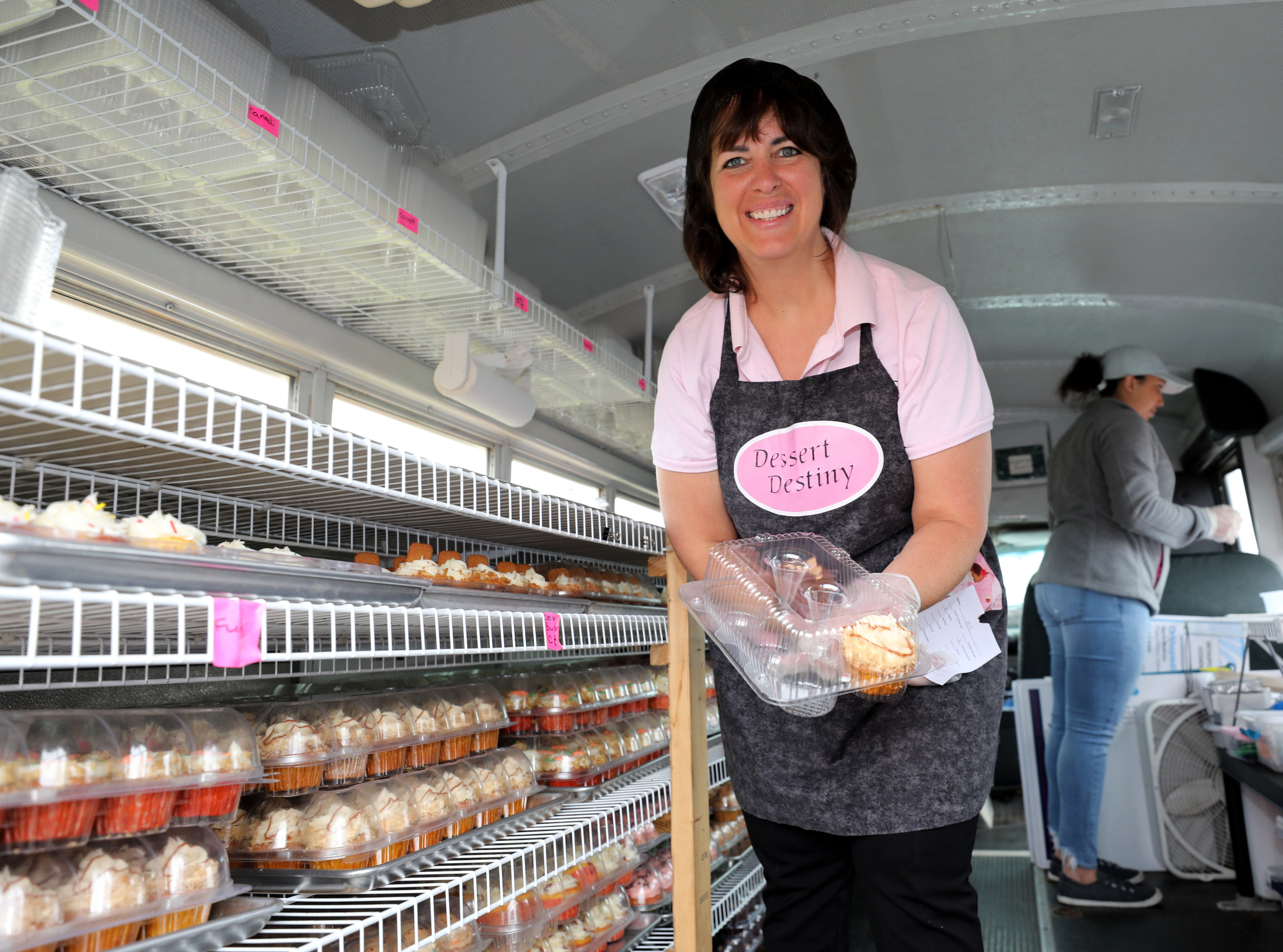 Tina Plass with the Dessert Destiny cupcake booth, gathers selections of cupcakes, during the K104.7 Cupcake Festival at the Stormville Airport, May 4, 2019.