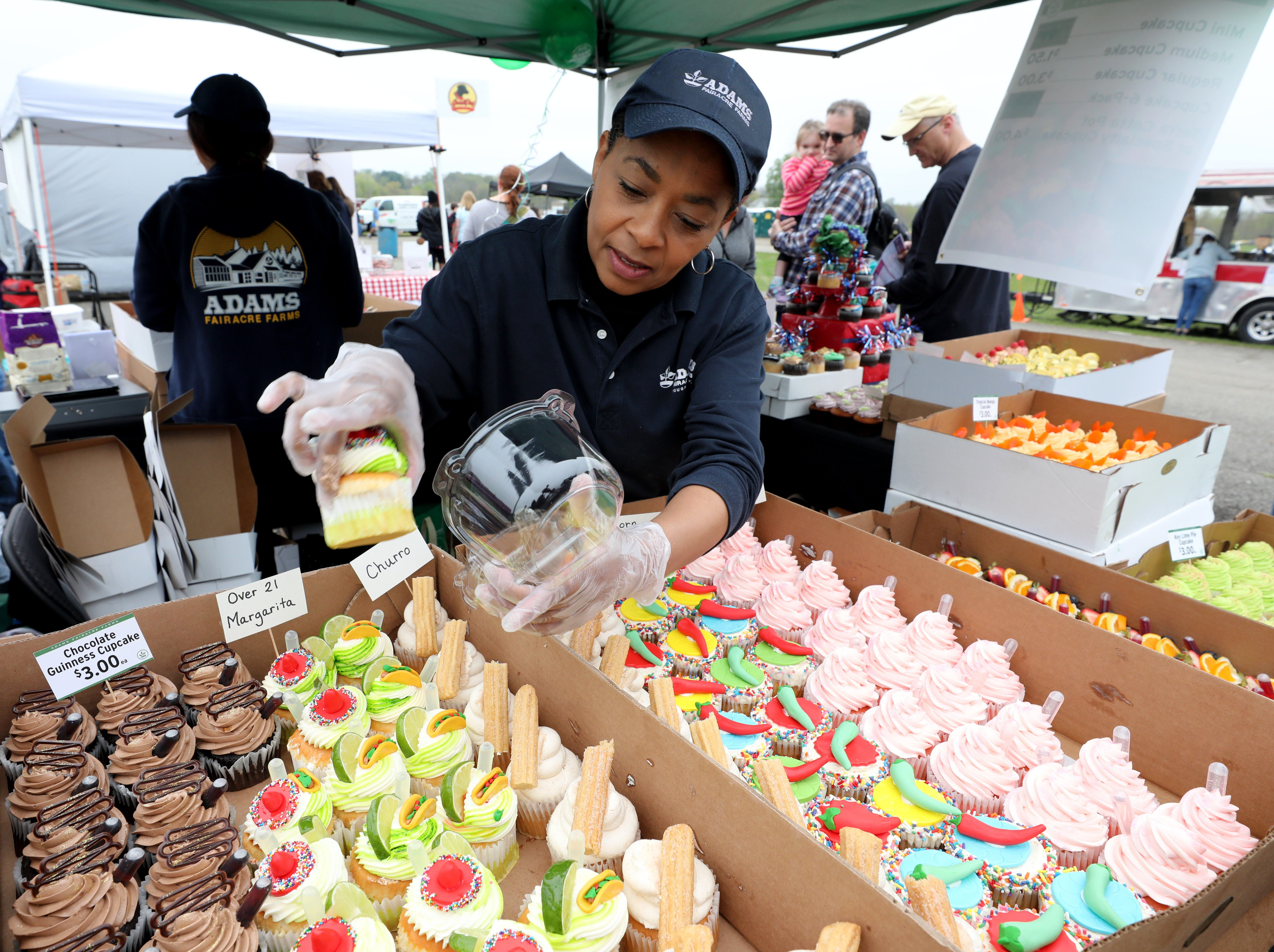 """Kay Taylor with the Adam's Fairacre Farms booth, selects an """"Over 21 Margarita"""" cupcake for a customer, during the K104.7 Cupcake Festival at the Stormville Airport, May 4, 2019.  See more photos and a video at Poughkeepsiejournal.com."""