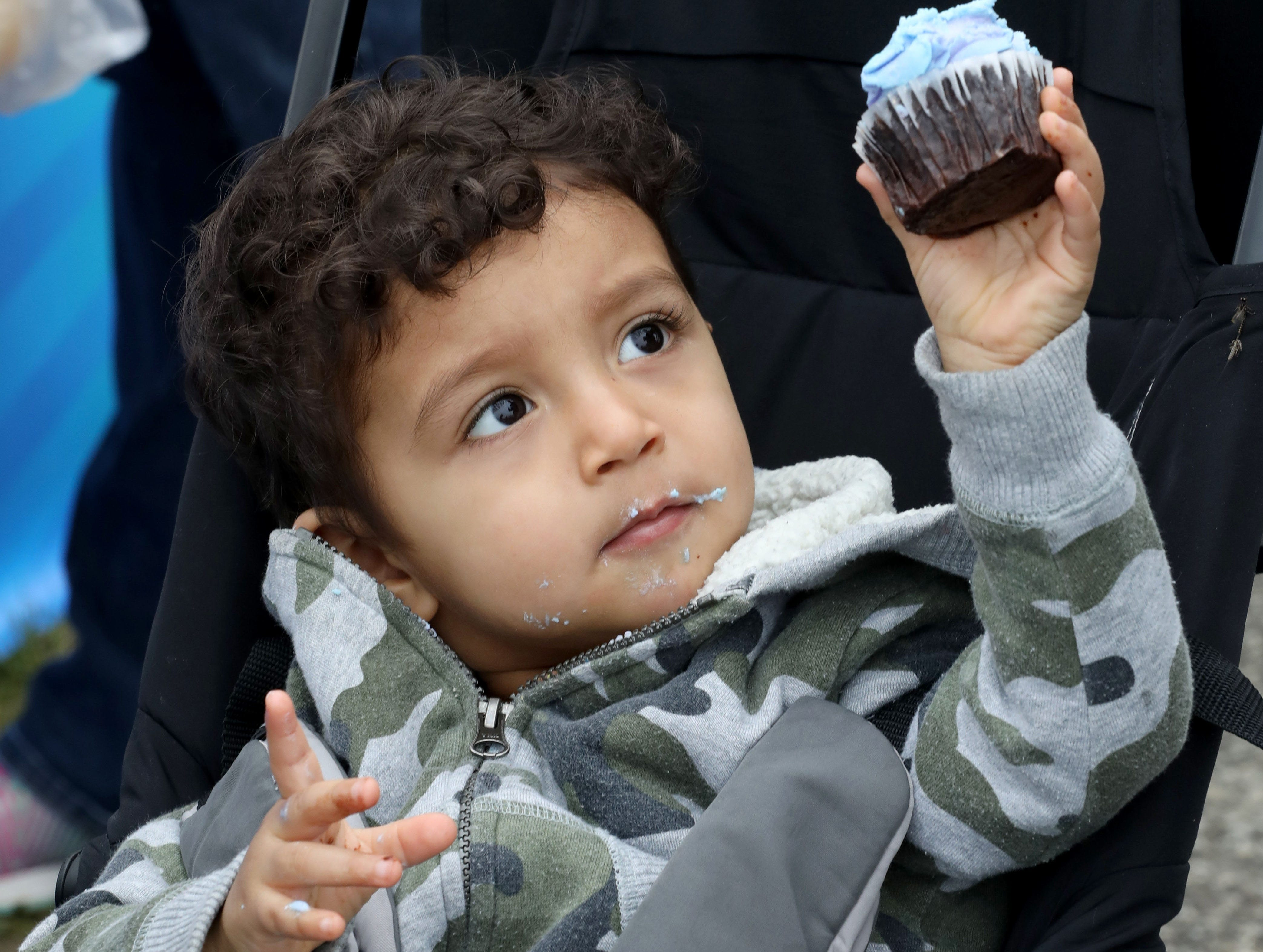 Asher Rodriguez, 2 from Newburgh, holds up his cupcake during the K104.7 Cupcake Festival at the Stormville Airport, May 4, 2019.