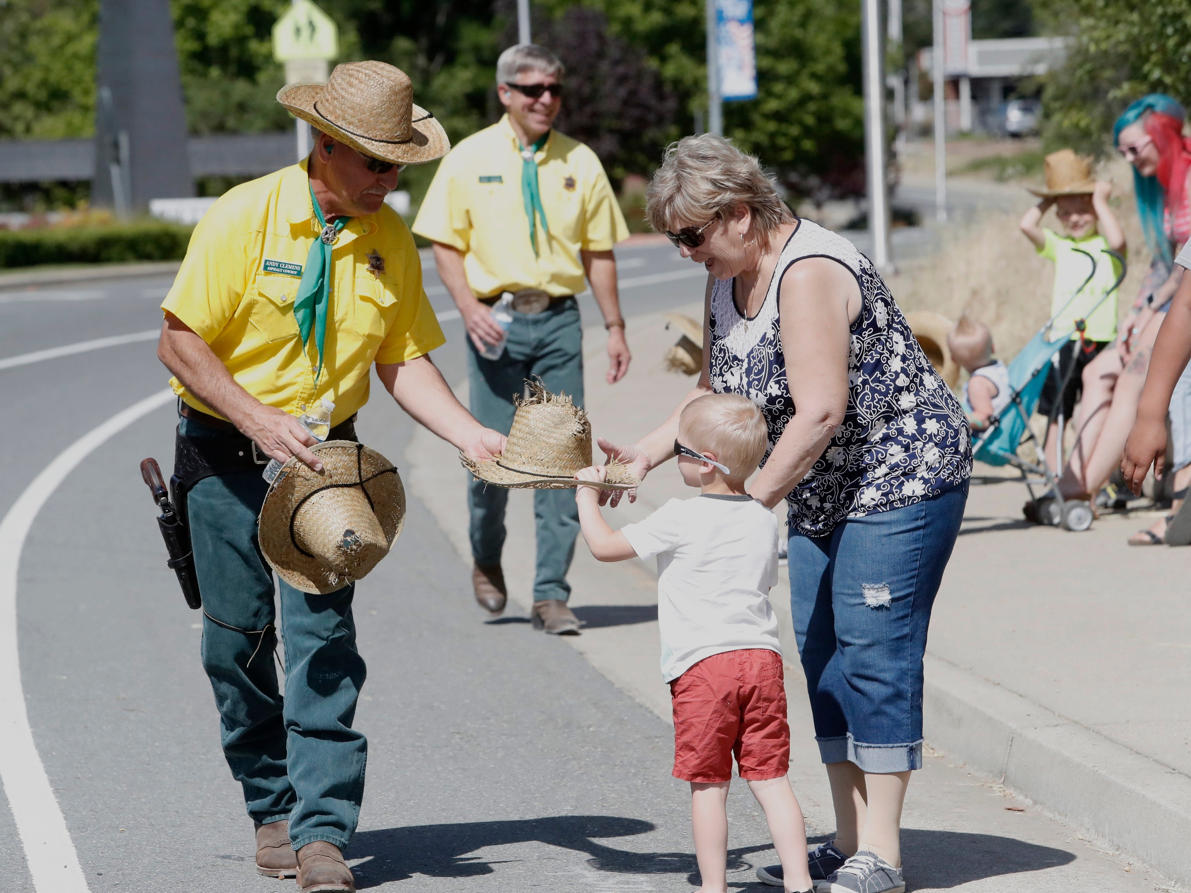 Asphalt Cowboy Andy Clemens hands a straw hat with its top shot out to 3-year-old Korben Pavlovich of Redding as grandma Claudia Knerr helps out during the Boomtown Festival parade in Shasta Lake on Saturday, May 4, 2019.