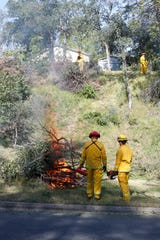 Redding firefighters clear a city-owned hillside along Blazingwood Drive to help protect the neighborhood against fire during Wildfire Community Preparedness Day on Saturday, May 4, 2019.