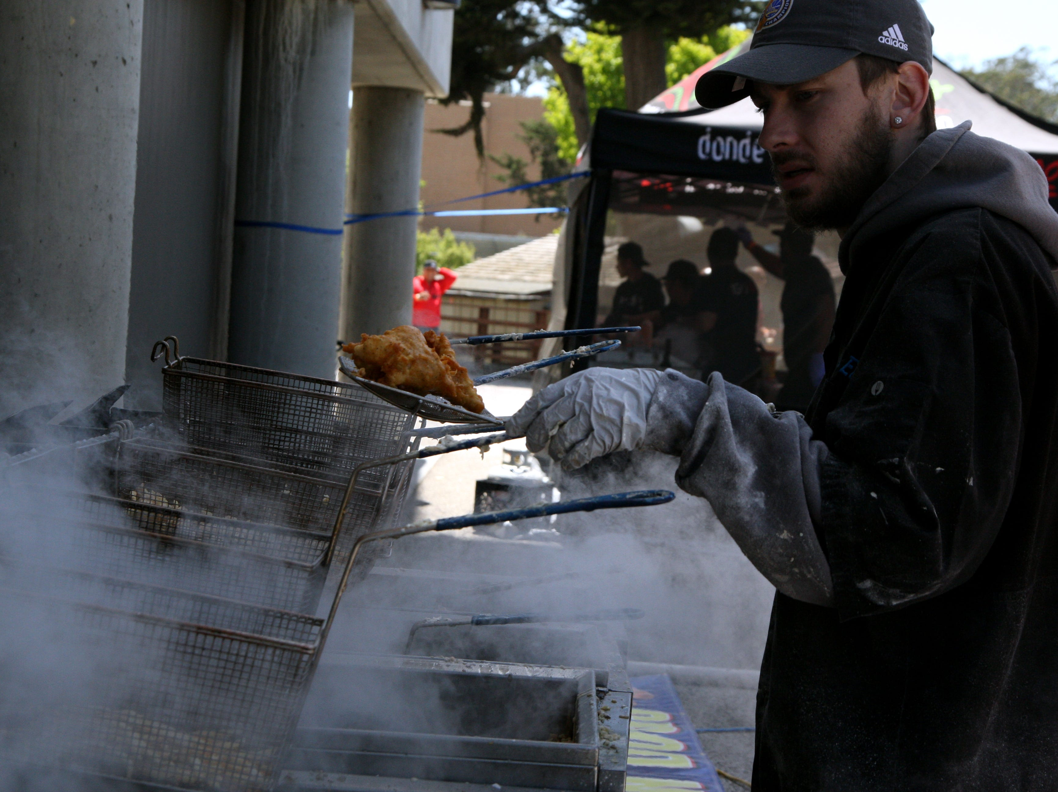 A fry cook pulls fried fish out of the fryolator as smoke billows from the hot grease. May 4, 2019.