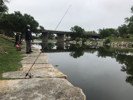 A pole is set up to catch catfish as Will Robinson and his kids enjoy the day at the Concho River Saturday, May 4, 2019.
