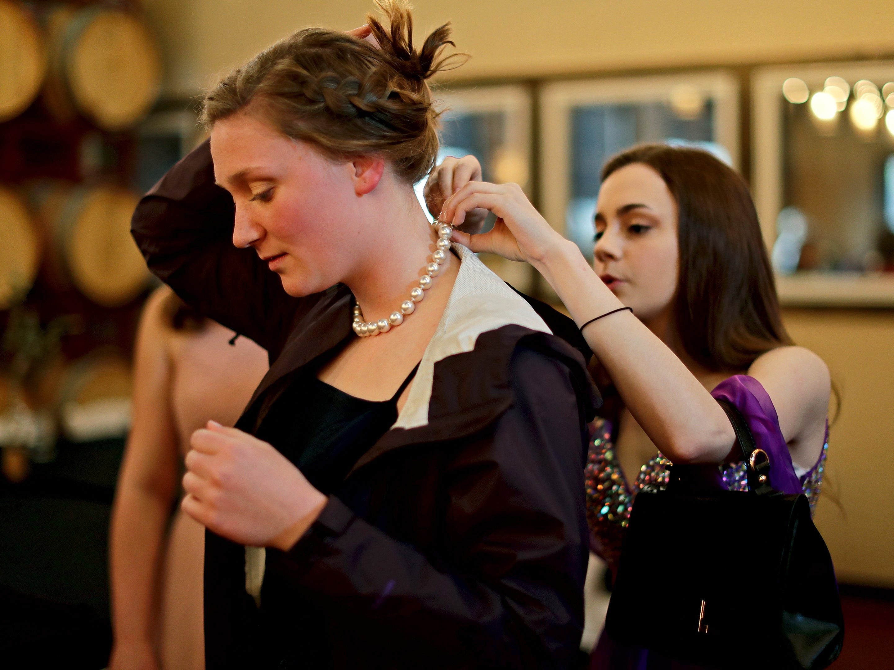 Annie Cornette, right, attaches a necklace on Ellie Steenwyk before the Sheboygan Christian Junior-Senior Banquet, Friday, May 3, 2019, at The Blind Horse, in Kohler, Wis.