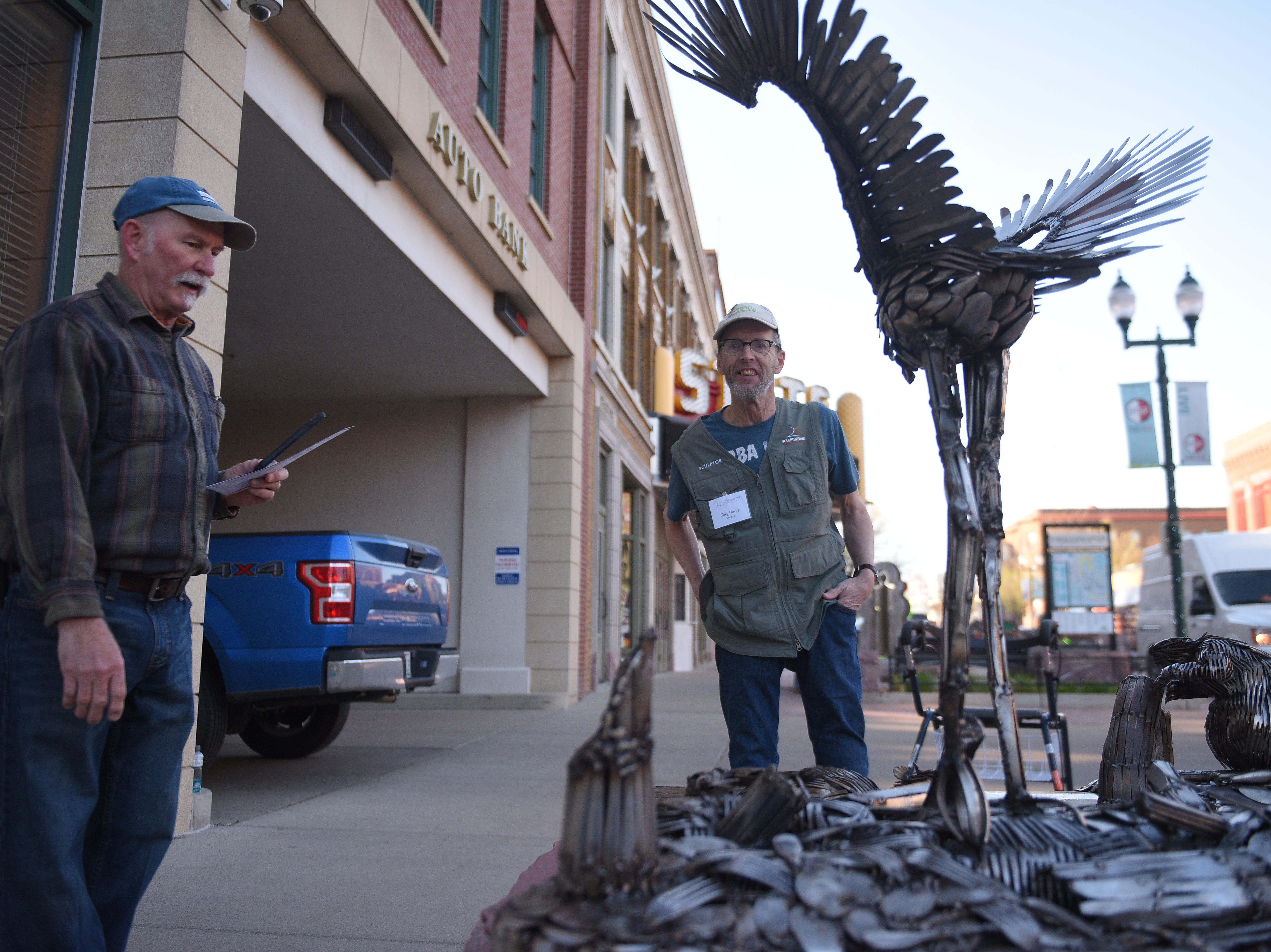 "Gary Hovey, right, stands by his sculpture, ""Under Construction"", after its installation for the 16th Annual SculptureWalk in downtown Sioux Falls Saturday, May 4."