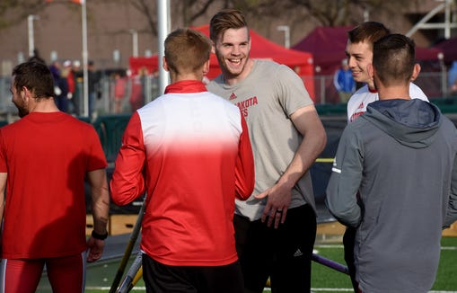 University of South Dakota junior Chris Nilsen, center, jokes with teammates  during the Howard Wood Dakota Relays Friday in Sioux Falls. Multiple weather delays pushed much of the meet into the evening hours, and Nilsen's eventual win in the men's pole vault would come hours later, and was one of the final events of the night.