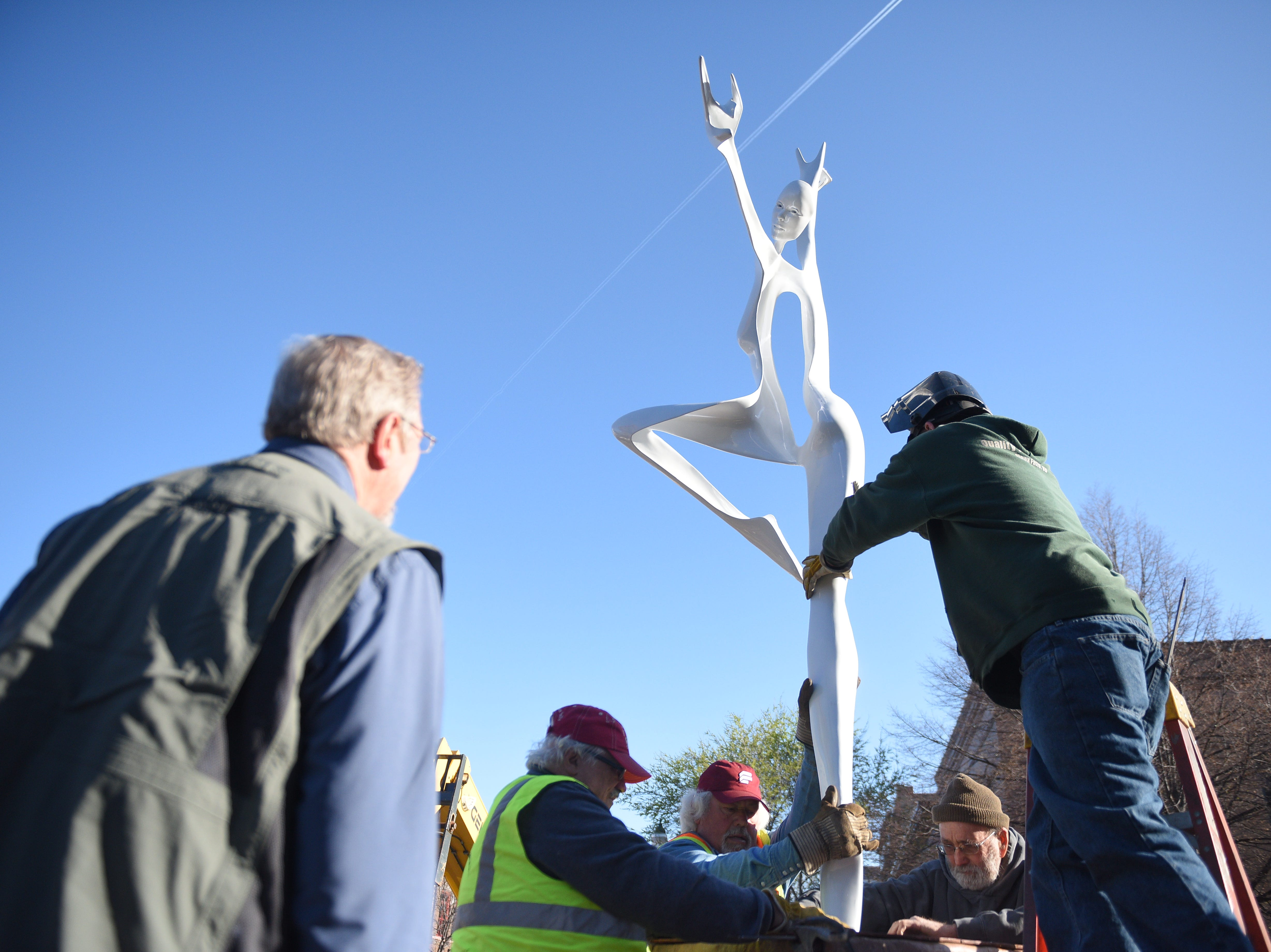 "Harold Linke, of Evergreen, Colorado, watches as crews install his sculpture, ""Spiral Dance,"" on Saturday, May 4, 2019, for the 16th Annual SculptureWalk Sioux Falls."