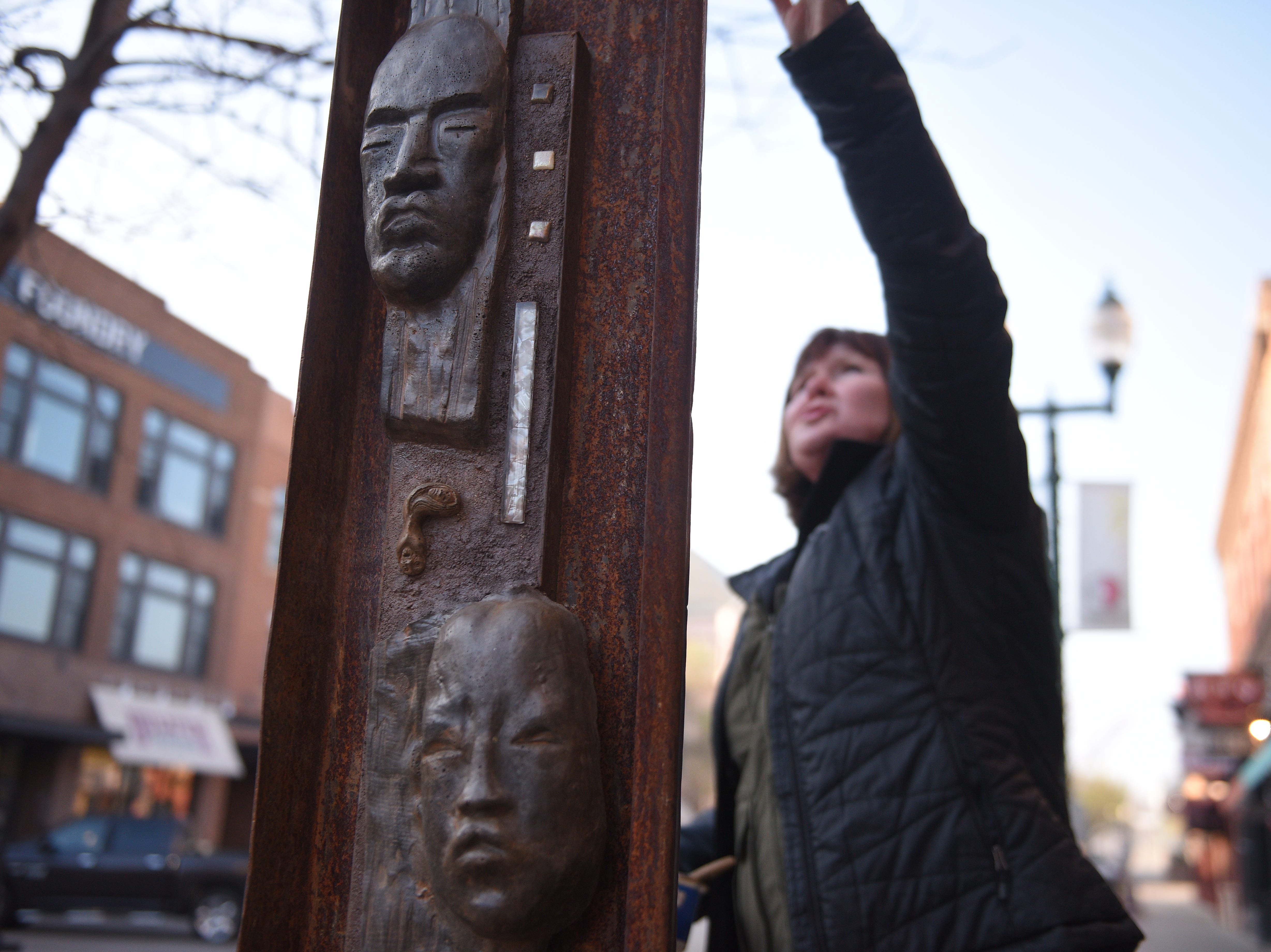 "Sue Quinlan, of Boulder, Colorado, seals the concrete on her sculpture, ""Ancient Monolith"" to help it survive the winter months. Quinlan's sculpture is one of 59 in the 16th Annual SculptureWalk Sioux Falls installed on Saturday, May 4."