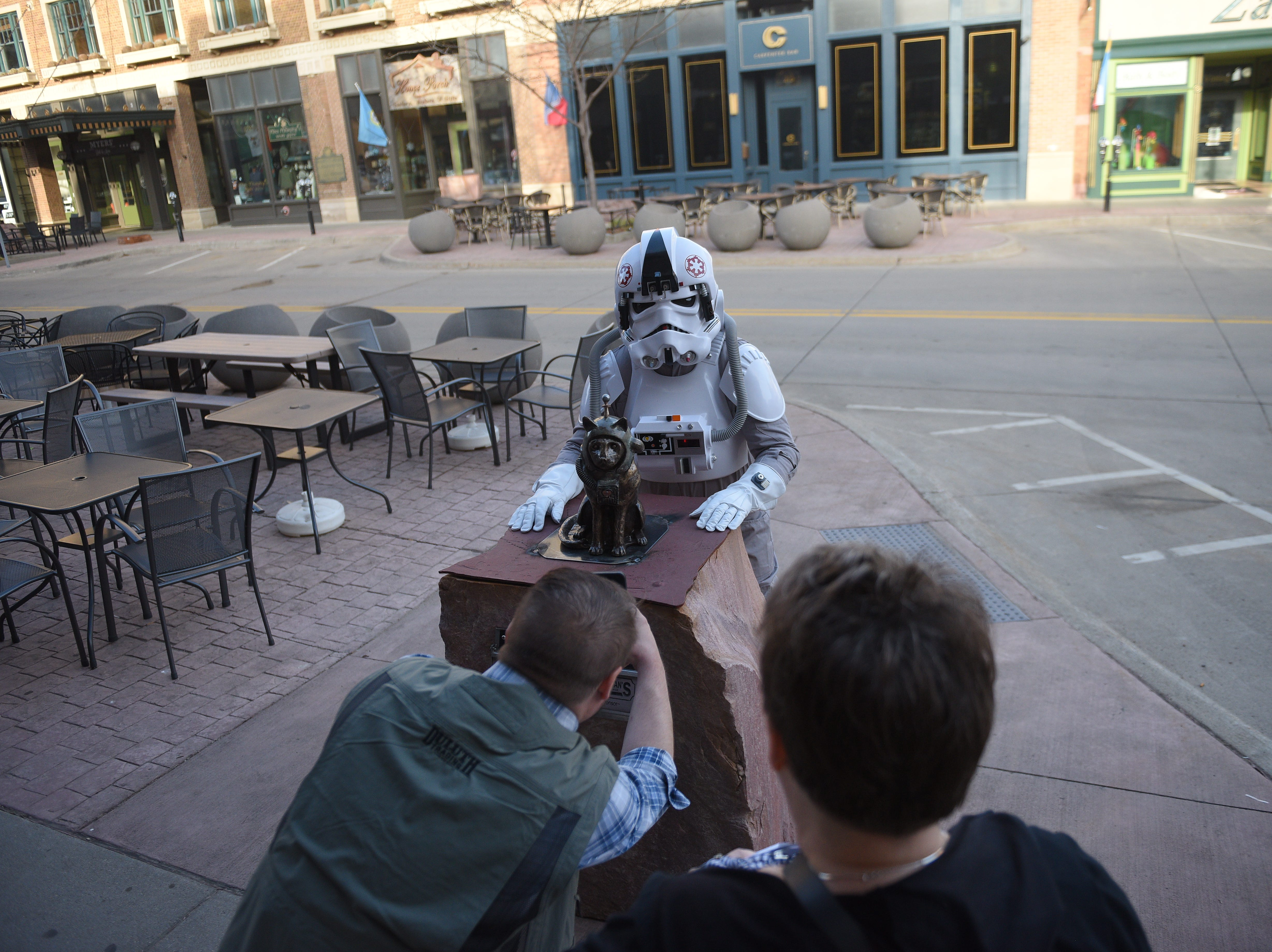 "Artist Anthony Guntren takes a photo of his sculpture, ""Space Cat"", with a Storm Trooper Saturday, May 4, 2019. ""Space Cat"" is one of 59 new sculptures for the 16th Annual SculptureWalk Sioux Falls."
