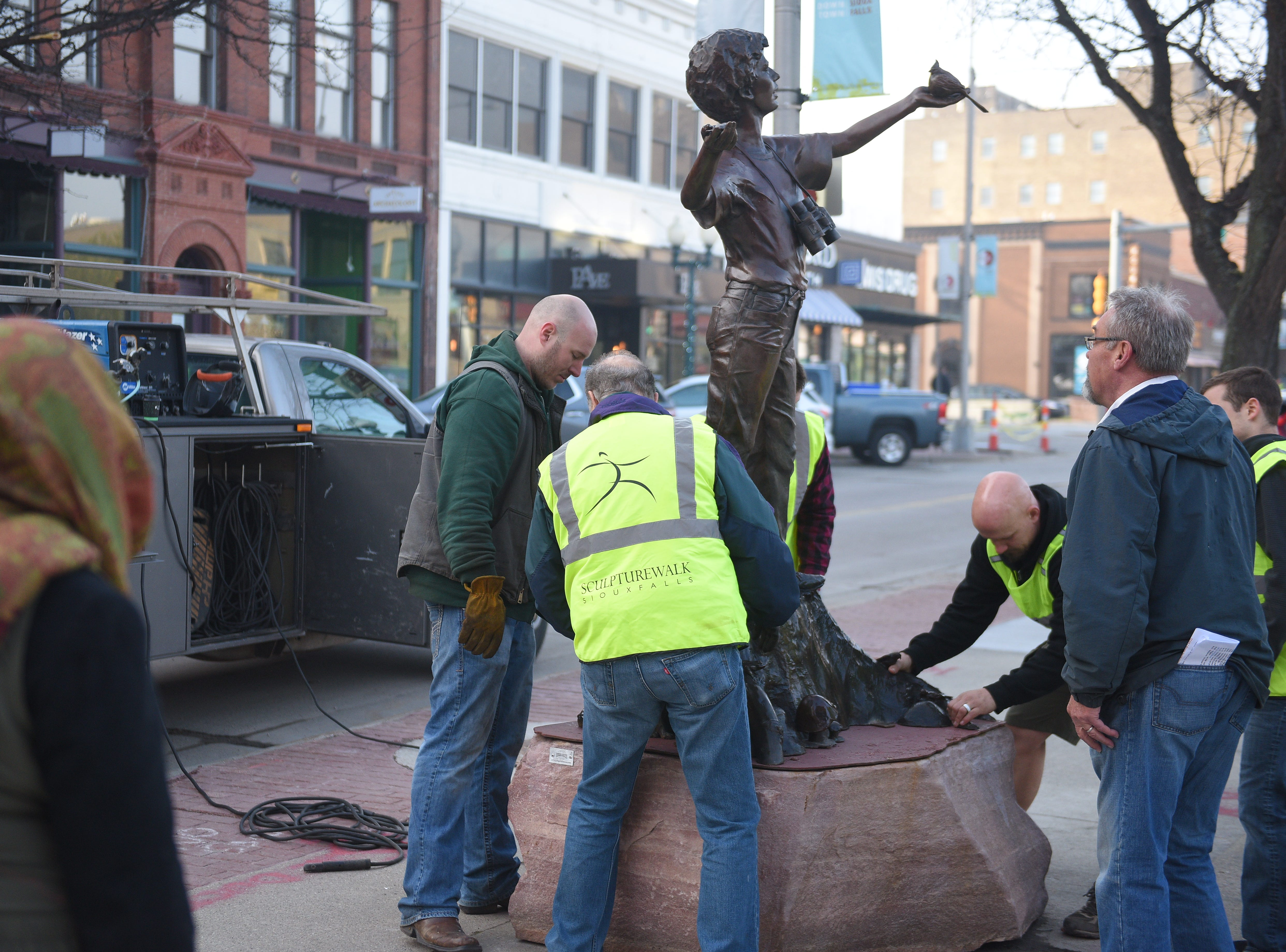 Bobbie Carlyle watches as SculptureWalk Sioux Falls crews install her sculpture on Phillips Avenue the morning of Saturday, May 4, 2019, as part of the 16th Annual SculptureWalk Sioux Falls.