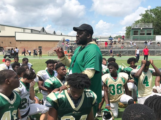 Lincoln High School football head coach Quinn Gray talks with his players after a scrimmage on Saturday, May 4, 2019.