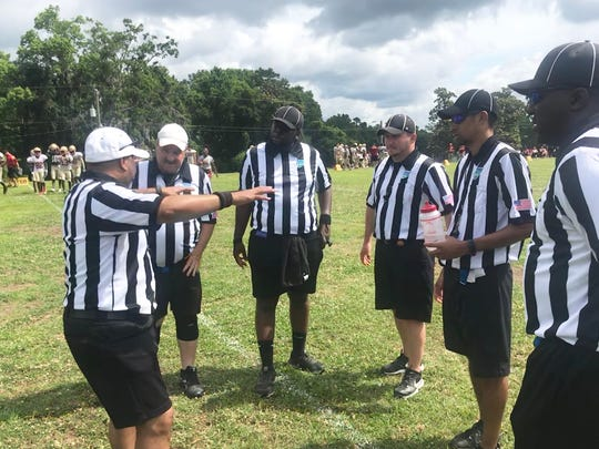 Referee Dante Sailor (far left) explains things to look out for to his crew during a scrimmage at Lincoln High School on Saturday, May 4, 2019.
