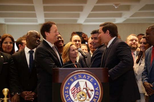 Gov. Ron DeSantis shakes hands with Senate President Bill Galvano before speaking after Sine Die Saturday, May 4, 2019.